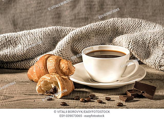 Coffee with croissants on the background of a woolen scarf. Grains of coffee next to the cup. Several pieces of dark chocolate next to each other