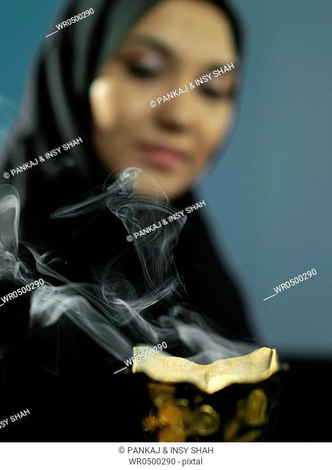 An Arab lady smells the aroma of incense