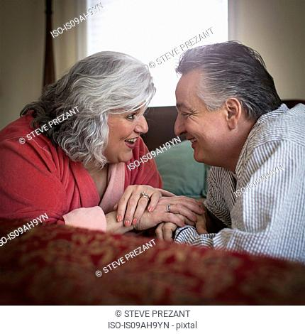 Affectionate mature adult couple lying on bed
