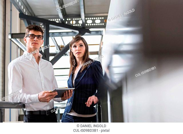 Two colleagues in industrial building, using digital tablet