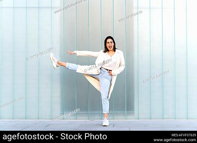 Cheerful businesswoman with stretching leg and arm while standing against glass wall