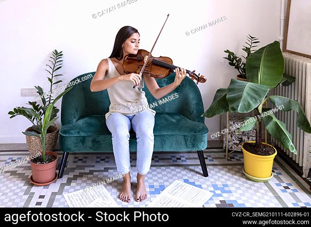 Sitting girl plays the viola, sheet music surrounds her bare feet