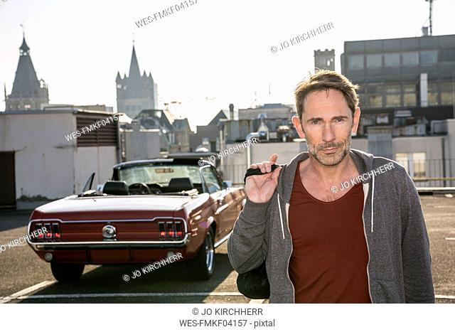 Germany, Cologne, portrait of mature man in front of his parked sports car on parking level