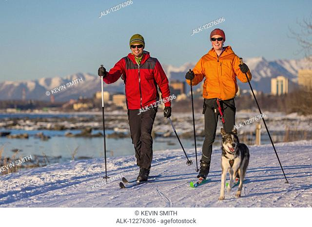 Two people cross country ski and skijor with an Alaska Husky on the Tony Knowles Coastal Trail near Earthquake Park with Anchorage skyline in the background