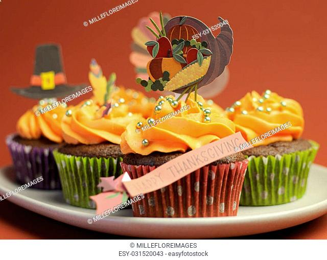 Happy Thanksgiving cupcakes with turkey, feast, and pilgrim hat topper decorations against a harvest red brown background