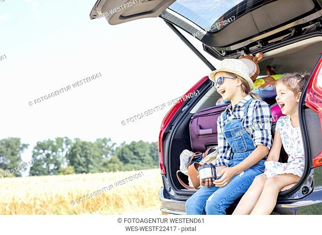 Two girls sitting in open car boot drinking tea