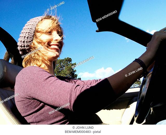 Hispanic woman driving convertible
