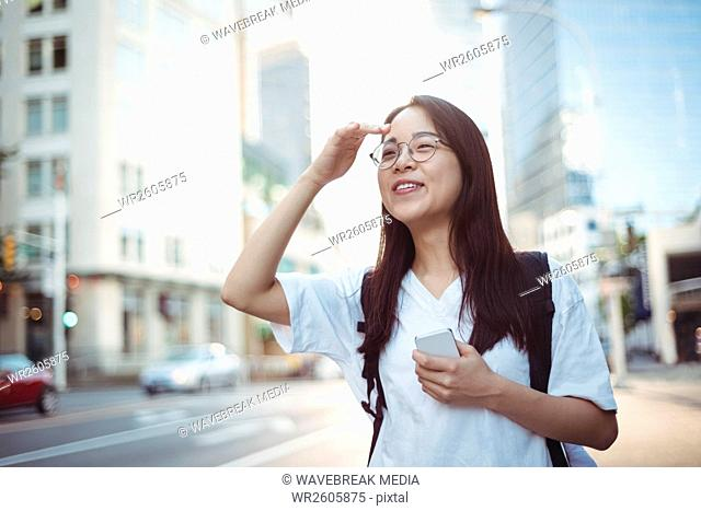Young woman shielding her eyes on street