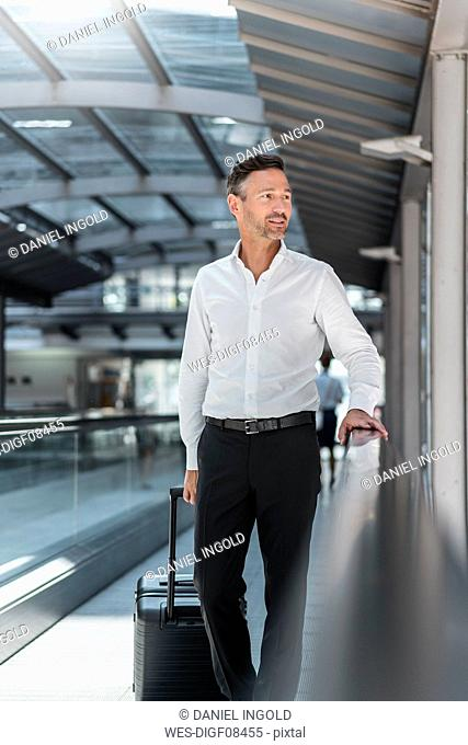 Businessman on moving walkway at the airport