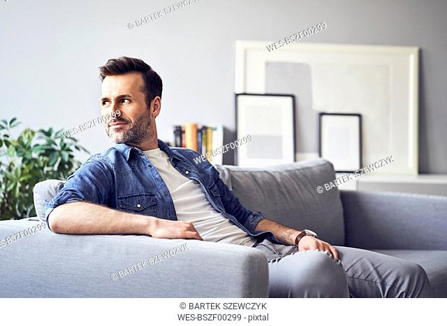 Smiling relaxed man sitting on sofa looking away