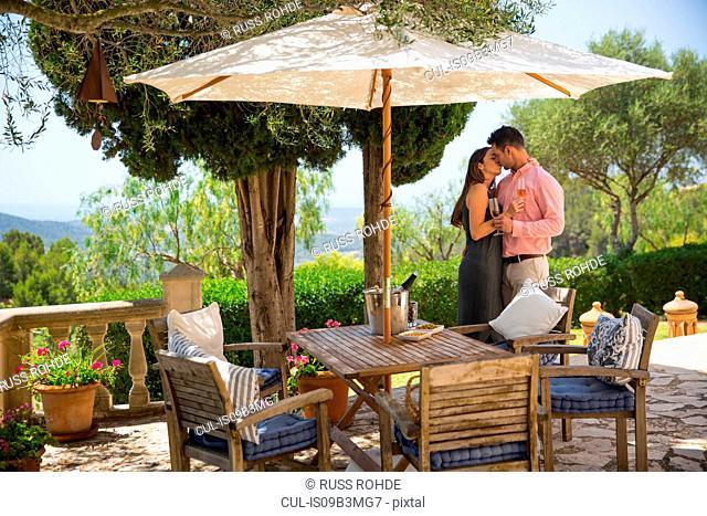 Romantic couple kissing on patio at boutique hotel, Majorca, Spain