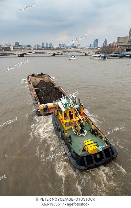 Tug pushing rubbish barge on River Thames in London