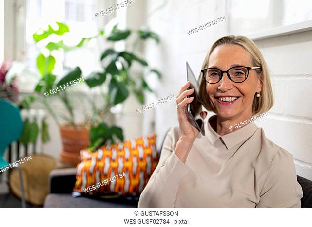 Smiling mature businesswoman using tablet in office lounge