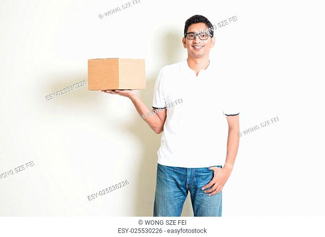 Indian man smiling and holding delivery courier box, standing on plain background with shadow. Asian handsome guy model