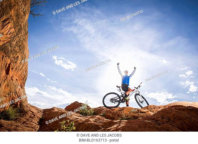 Caucasian man cheering on mountain bike on mountain
