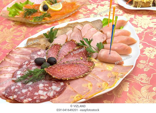 Different meat delicacies in a plate on a server table close-up. Cutting of different types of sausage and meat