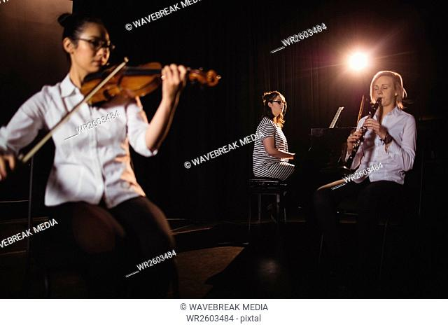 Three female students playing piano, clarinet and violin