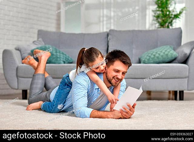 happy child daughter congratulates her father and gives him postcard. Dad and little girl smile and hug. father's day
