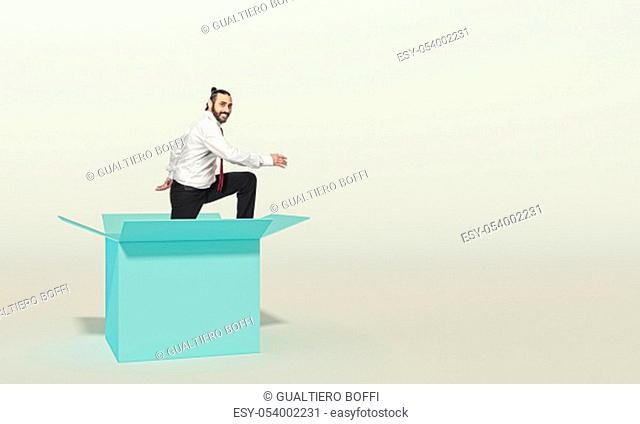 smiling businessman looks in the room as he comes out of a box. concept of different thinking and innovation