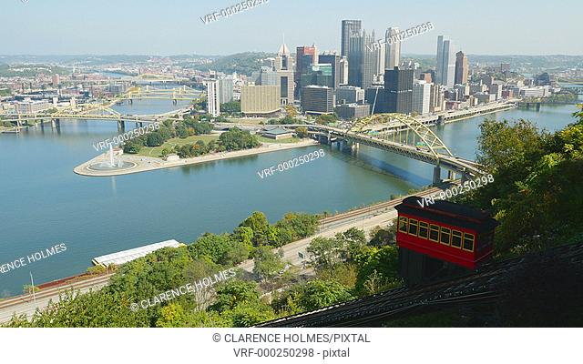 The Duquesne Incline descends Mt. Washington with a view of the downtown area including the skyline, bridges, and Point State Park at the confluence of the...