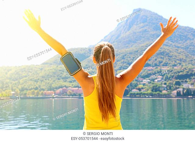 Success fitness woman concept with sports armband for phone. Winning concept of female athlete runner cheering with arms raised up for achievement in weight...