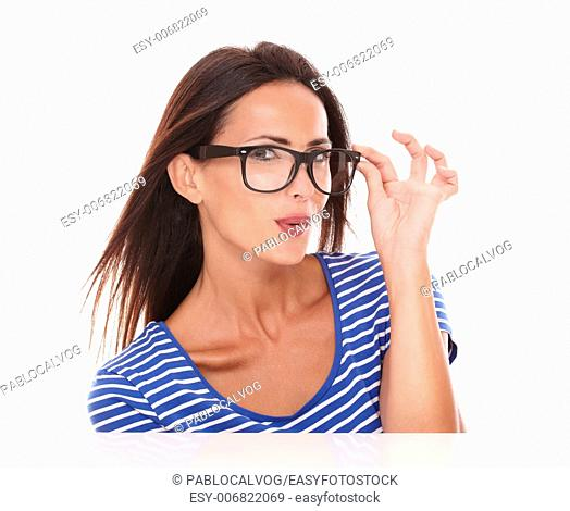 Beautiful lady holding spectacles while smiling and looking at camera in white background