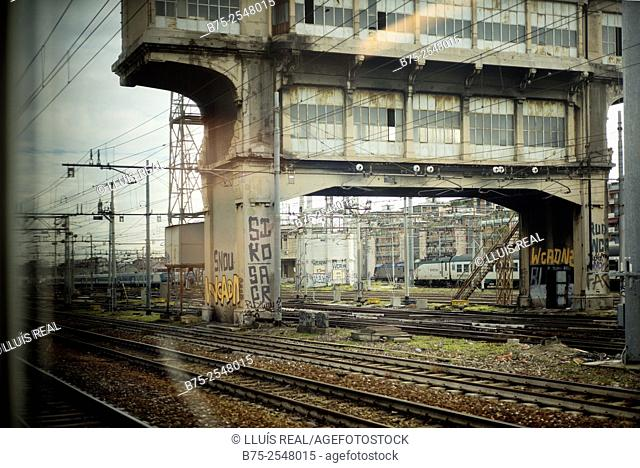 View from the window of a train, arriving to Milano of rail tracks, poles with electrical wires, a train and a decadent old building from the train Station in...