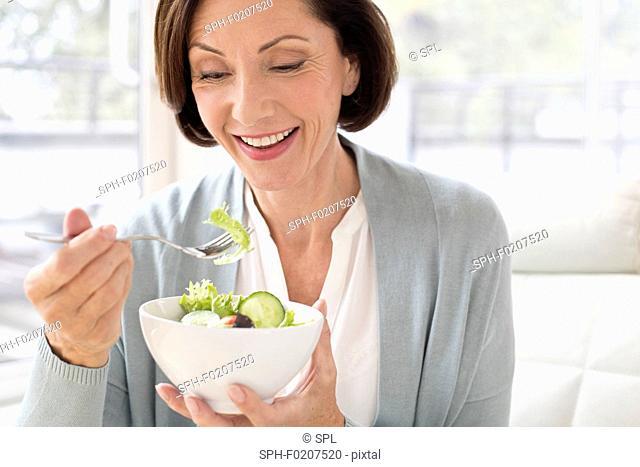 Mature woman eating salad