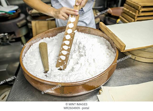 A small artisan producer of wagashi. A man mixing a large bowl of ingredients and pressing the mixed dough into moulds in a commercial kitchen