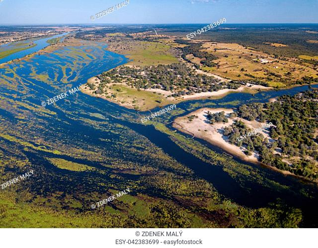 Aerial landscape in Okavango delta on Namibia and Angola border. River with shore and green vegetation after rainy season. Africa aerial landscape