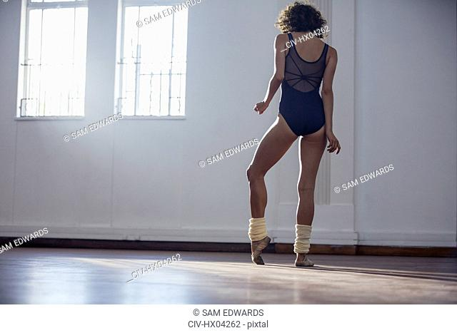 Graceful young female ballet dancer stretching foot in dance studio