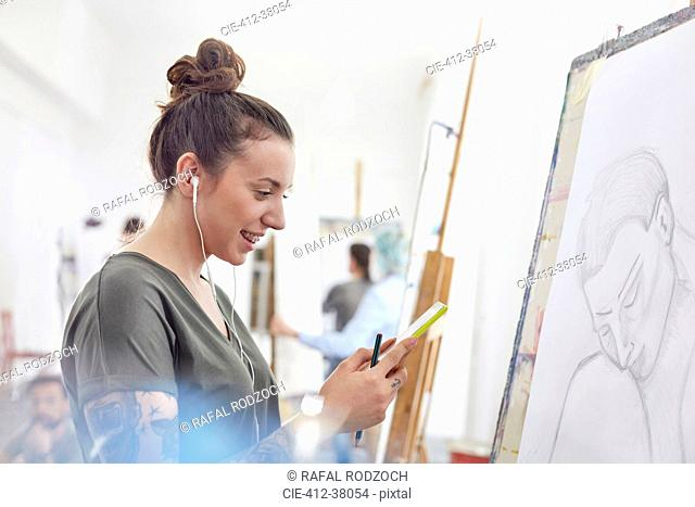 Smiling female artist with headphones listening to music and sketching in art class studio