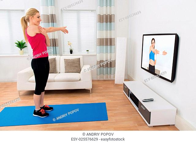Young Woman Exercising In Front Of Television In Living Room