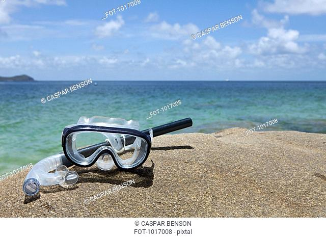 A diving mask and snorkel on a rock near the sea