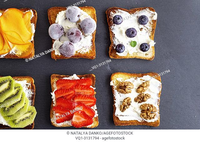 French toasts with soft cheese, strawberries, kiwi, walnuts and blueberries on a black board, top view.  New Image Data