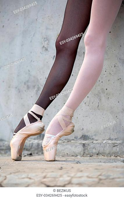 Photo of the young graceful ballerina feet close-up on a background of textured concrete wall. Legs dressed in different colored tights black and white