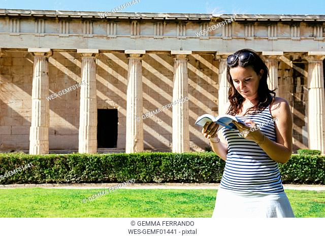 Greece, Athens, woman reading a book in front of The Hephaisteion in the Agora