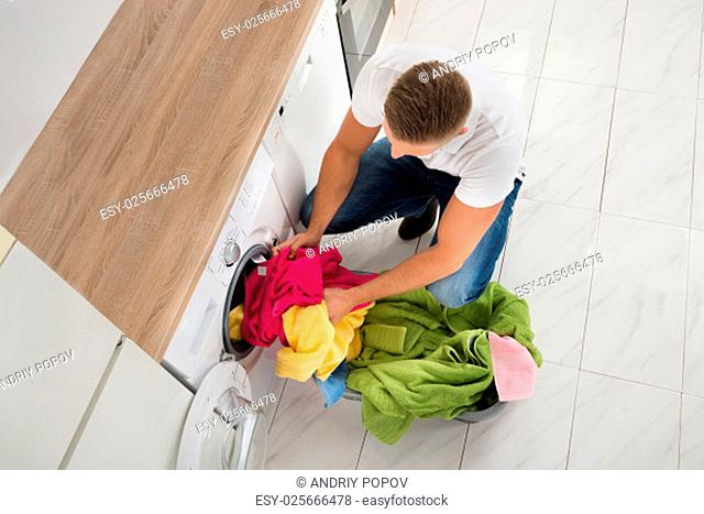 High Angle View Of Young Man Putting Clothes In Washing Machine