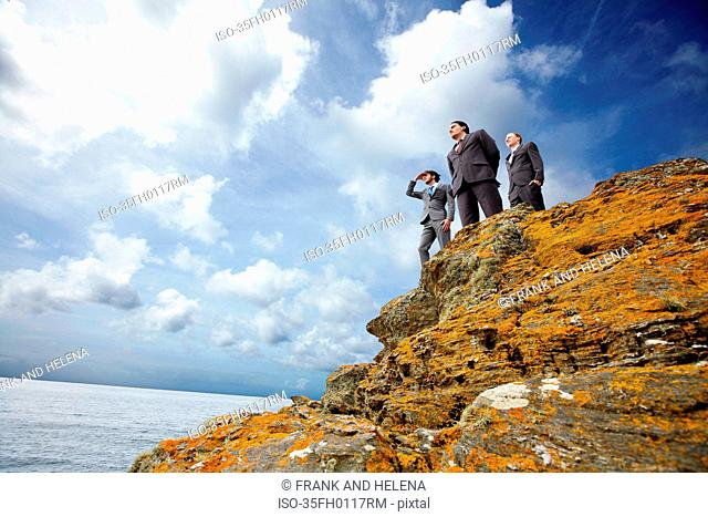 Businessmen standing on cliff edge