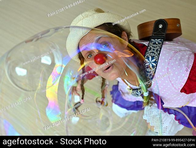 "19 August 2021, Brandenburg, Burg: Clown Hella Proppela from Lachen hilft e.V. looks through a soap bubble in the children's hospice """"Pusteblume"""" run by..."