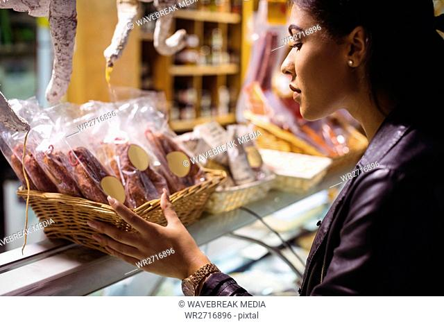 Woman selecting sausage at meat counter
