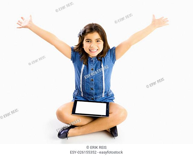 Young girl sitting on floor and using a tablet