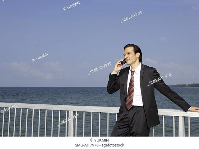 Businessman leaning on railing, using mobile phone