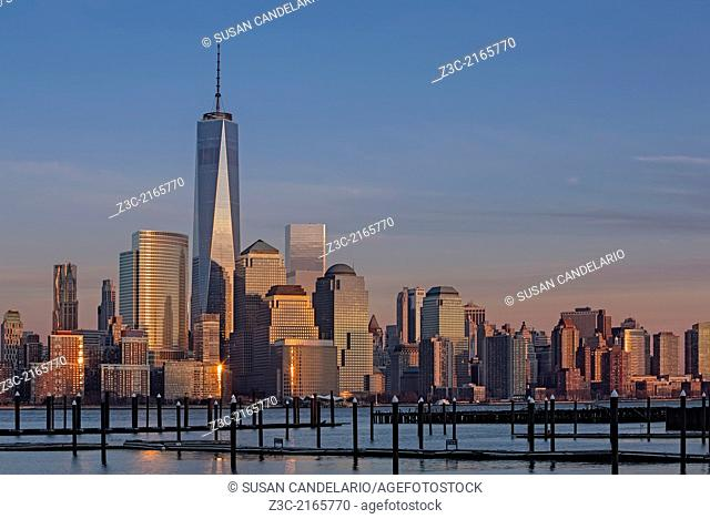 Lower Manhattan Skyline in New York City during sunset as seen from across the Hudson River in New Jersey. Along with One World Trade Center are other...