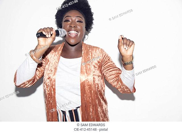 Portrait young woman with microphone singing
