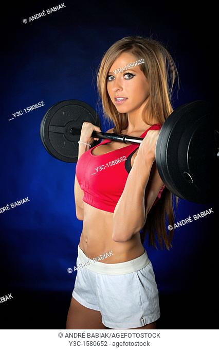 Pretty woman at fitness training with workout bar