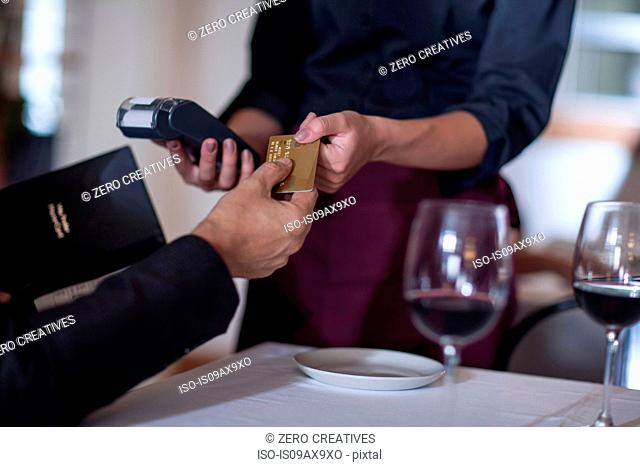 Customer paying with credit card to waitress in restaurant