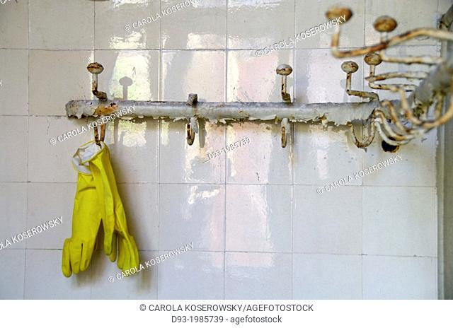 Pair of yellow Rubber gloves hanging on coat hook in an abandoned Hospital near Berlin Germany