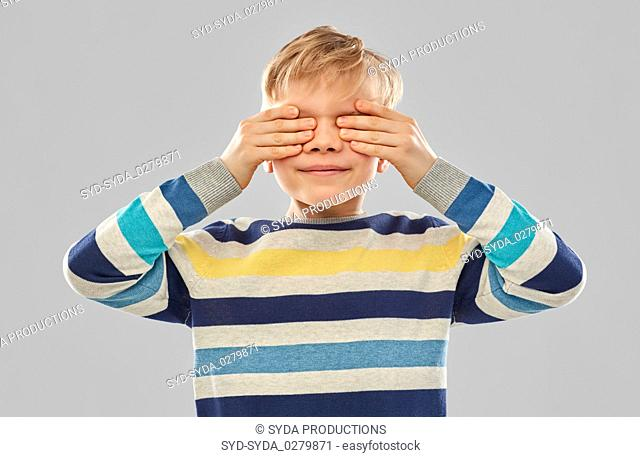boy in striped pullover closing his eyes by hands
