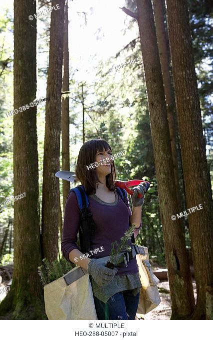 Smiling tree planting volunteer in woods
